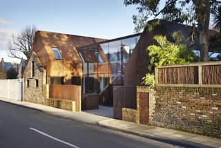 """Weathered Steel Clads a $4.7M Home Near London's Kew Gardens - Photo 1 of 10 - """"Kew House was conceived as an interplay between the rustic exterior of weathering steel and retained stable wall and the refined, light interior,"""" says Piercy, """"the glazed circulation link revealing the contrast from inside and out."""""""