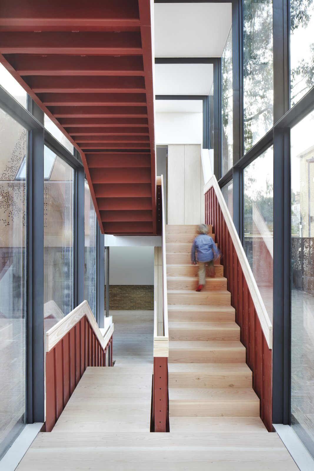 An exposed steel staircase in a glazed circulation link connects the two living wings.