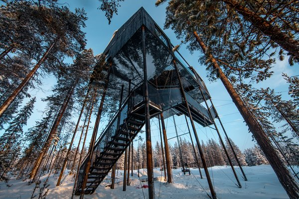 Photo Essay: Enchanting Tree Houses - Photo 15 of 24 - Designed by the renowned firm Snøhetta, the structure hovers 10 meters above the ground with a black-and-white print of the canopy covering the bottom façade, creating a trompe l'oeil effect. The two bedrooms, bathroom, lounge area, and netted terrace are arranged across two slightly different levels, accommodating up to five guests.