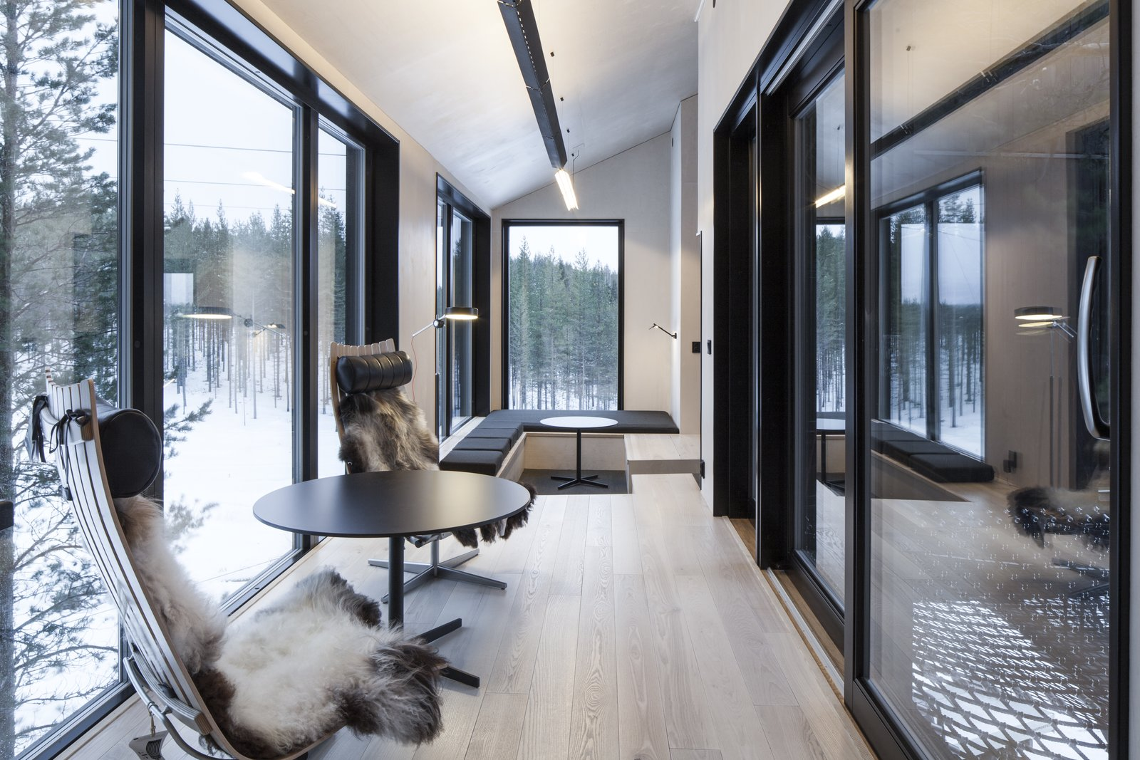 Light ash flooring and birch plywood walls create a light interior that contrasts the dark, charred exterior wood. Here in the lounge space, simple furniture such as the Scandia Chair by Hans Brattrud and a central pellet stove create a calm, inviting environment. A floor-to-ceiling window, facing north, is your best bet for seeing the Aurora Borealis. Tagged: Living Room, Light Hardwood Floor, and Chair.  Photo 4 of 8 in Go Stargazing in Snøhetta's Towering Addition to Sweden's Treehotel