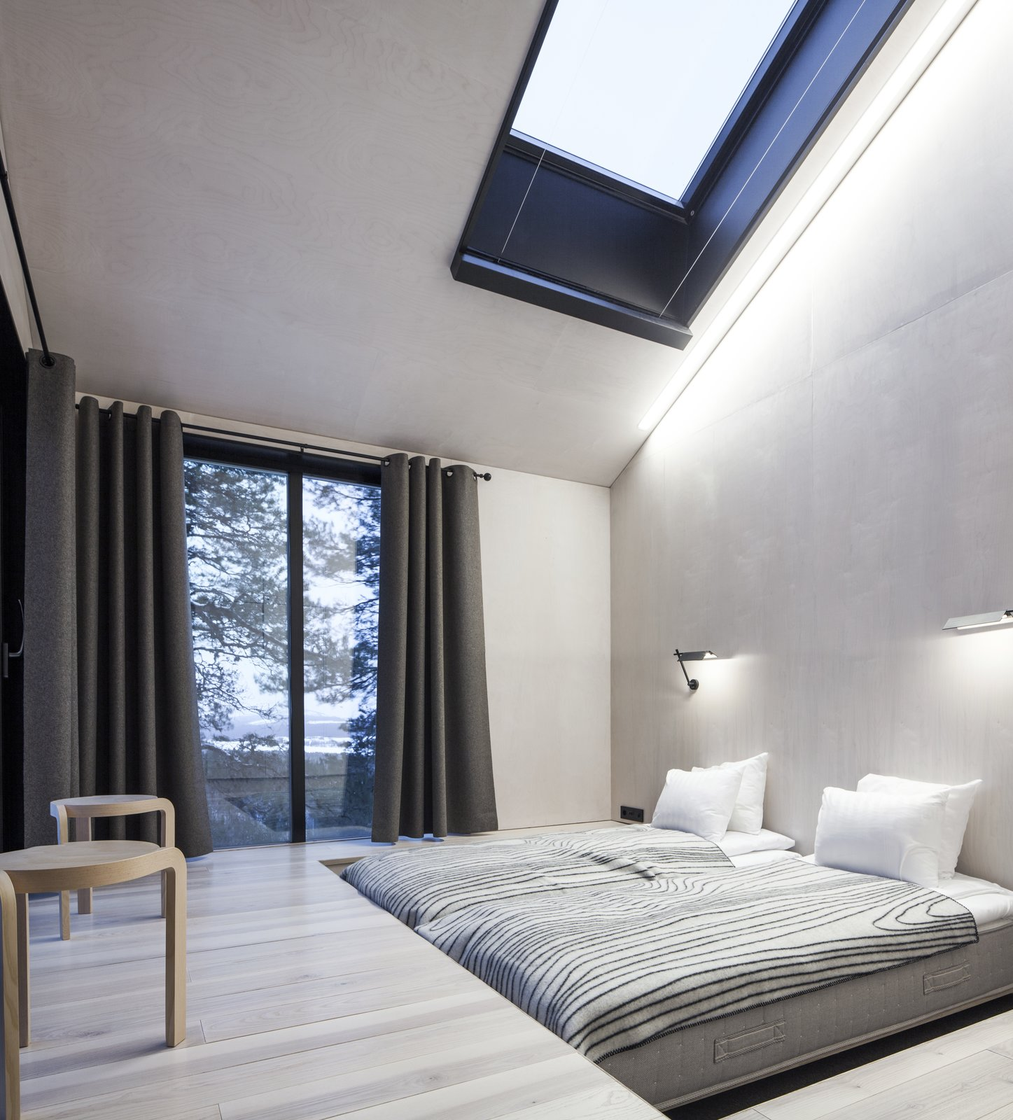 The bedrooms are placed on opposite ends of the cabin, each equipped with sliding doors that lead to the netted terrace. Above, skylights offer additional views of the stars. Tagged: Bedroom, Bed, and Light Hardwood Floor.  Photo 6 of 8 in Go Stargazing in Snøhetta's Towering Addition to Sweden's Treehotel