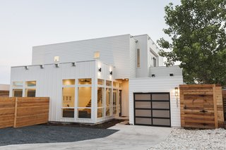 Dwell's Top 10 Upcycled Shipping Containers of 2017 - Photo 3 of 10 - The modular appearance of the duplex, clad in white Hardie plank siding, mimics the look of a two-story container home. With large windows and 11-foot-tall ceilings, the two-bedroom, three-bath residence feels more spacious than its 1,484 square feet. On the ground floor, the living, dining, and kitchen areas flow into one another; potential guests in the shipping container also have easy access to a full bath of their own. A steel-and-wood floating staircase leads to the second floor, which holds two bedrooms with patio access.