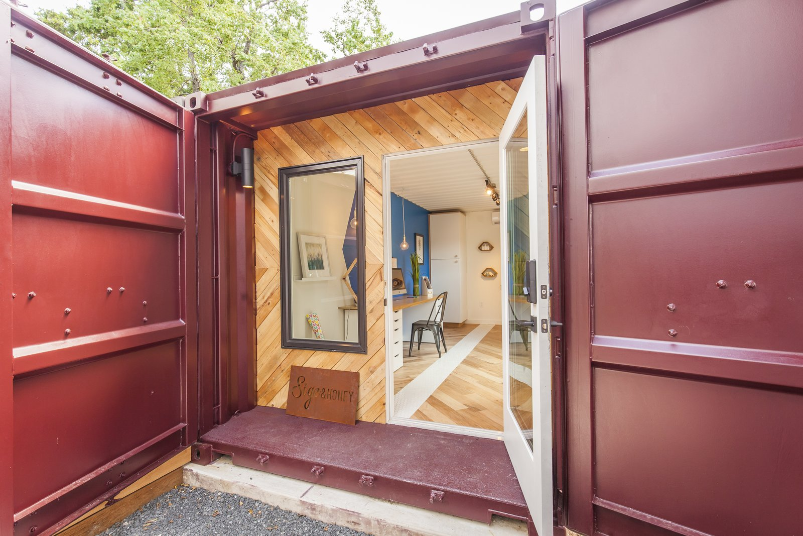 The front facade upcycles wood from the pallets used to ship in the cabinets.  Photo 9 of 10 in Ship Shape: An Austin Home With a Shipping Container Addition Asks $499K