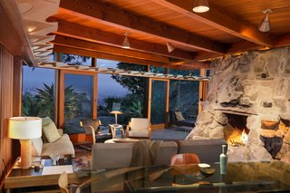 Find Seclusion in the City With This $2.5M Lloyd Wright Residence - Photo 5 of 7 - Another view of the living and dining area shows the stone fireplace and outdoor deck, which offers a commanding vista. A private wing extends from the common space and holds the bedrooms and bathrooms.