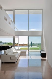 Spotlight on Portugal: 7 Epic Modern Spaces - Photo 1 of 7 - Known for long stretches of Mediterranean coastline, dramatic cliffs, and golf resorts, the southernmost region of Portugal has been a popular holiday destination since the '60s. A more relaxed alternative to tourist favorites, the resort town of Praia da Luz has a seat in western Algarve, offering sandy beaches and a thriving community of British expats. The open kitchen, dining, and living area boasts high ceilings above and natural stone tiles below. Sliding glass doors lead to the outdoor patio and heated pool.
