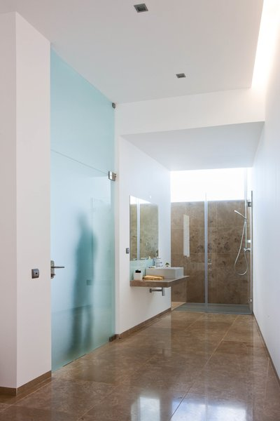The en-suite bathroom has a large bathtub, shower, and pre-installation for a steam or sauna room.
