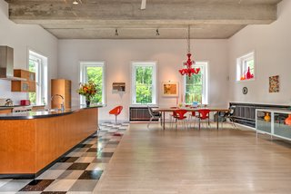 The first floor holds an integrated living room, dining room, and kitchen. When Reed and Blackburn bought the firehouse, the concrete floors were stained with oil from the firetrucks, so they laid stained white oak flooring. They also sandblasted the ceiling to its original concrete finish. A red Murano glass chandelier hangs over a vintage Danish dining table and Bernhardt Design Orbit Chairs.