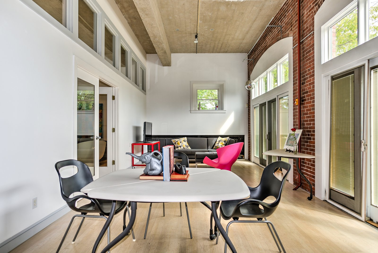 Towards the front of the house, where the original garage doors have been replaced by French doors and transom windows, is a multifunctional space with brick walls that currently functions as an office.