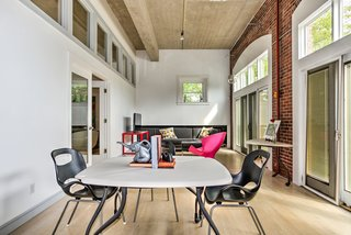 A Converted Firehouse Fit For an Artist Is Listed at $749K - Photo 4 of 8 - Towards the front of the house, where the original garage doors have been replaced by French doors and transom windows, is a multifunctional space with brick walls that currently functions as an office.