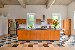 Reed designed the custom cabinets, which are made of lacewood and frosted glass. The kitchen also features a Bosch dishwasher and range hood, KitchenAid stove, and GE Profile refrigerator.