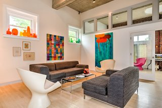 A Converted Firehouse Fit For an Artist Is Listed at $749K - Photo 3 of 8 - Label Kite Chairs by Karim Rashid flank either side of the living area. Clerestory windows let in additional light.