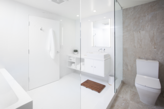 """""""We kept to a very simple and streamlined palette and carefully selected light fixtures that echoed the lines and movement within the space,"""" says Misra. The monochromatic bathroom features a custom white lacquer vanity and Porcelanosa tiles."""