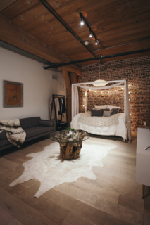 """The sleeping area is tucked into the back of the loft. Says Misra of the clients, """"As they moved in and felt the energy of the place, they admitted they could see themselves staying here more and more and commuting less and less."""""""