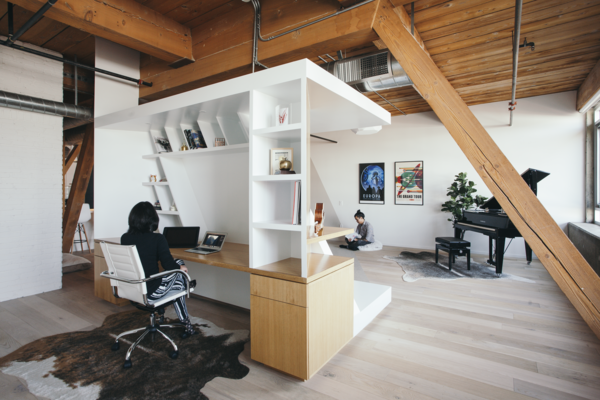 The Writer's Block is a piece of custom oak veneer millwork that both divides the space and acts as furniture.