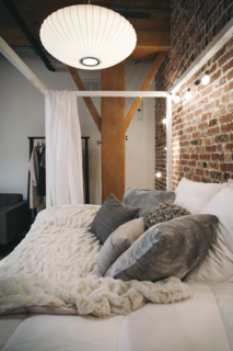 Step Inside One Couple's Game-Changing Live/Work Loft - Photo 9 of 9 - A George Nelson Saucer Lamp hangs over the bedroom.