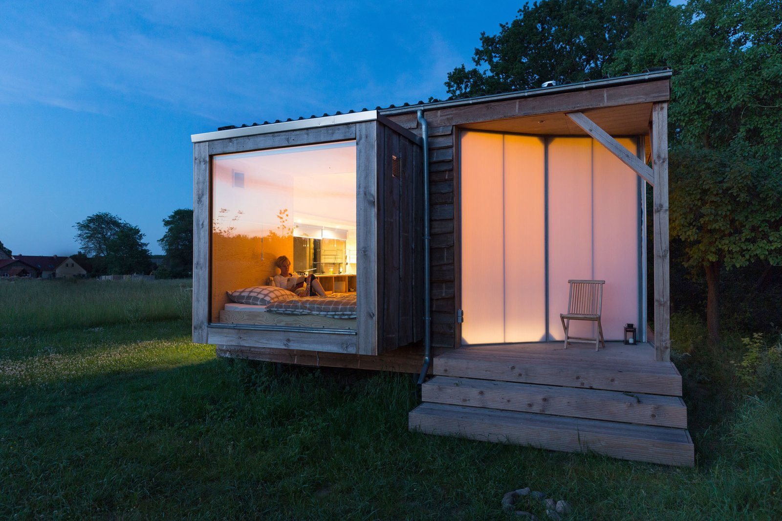 Suspended over the meadow, the bedroom boasts a large glass pane, while the transparent screen door allows the surrounding trees to cast playful shadows across it.