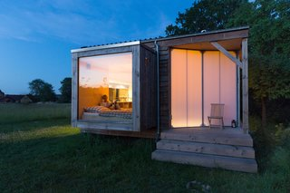 Rescuing a Historic Homestead, Two Artists Create a Rural German Retreat - Photo 9 of 9 - Suspended over the meadow, the bedroom boasts a large glass pane, while the transparent screen door allows the surrounding trees to cast playful shadows across it.
