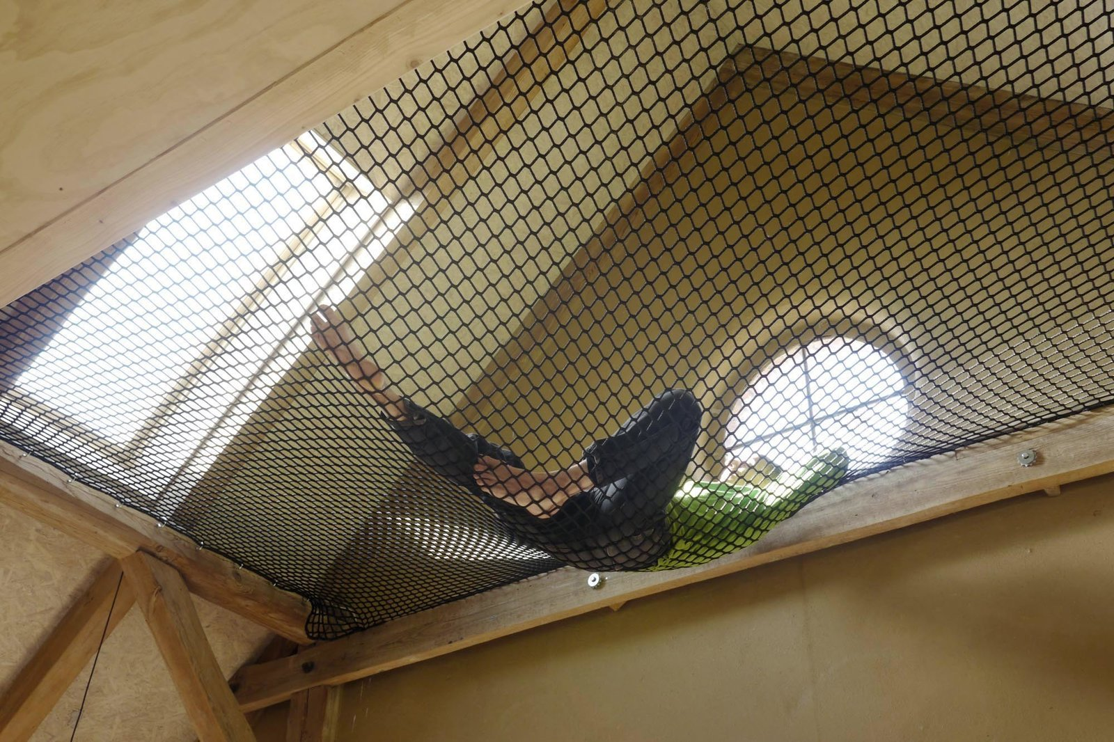 A hammock hung between beams, accessible from the mezzanine, provides a sunny spot to lounge. Rescuing a Historic Homestead, Two Artists Create a Rural German Retreat - Photo 4 of 10