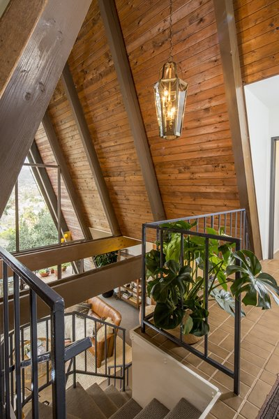 Upon entering, the foyer offers dramatic views of the San Gabriel Mountains straight ahead, framed by the wooden beams of the steeply pitched roof. On either side of the foyer are the master suite and second bedroom.