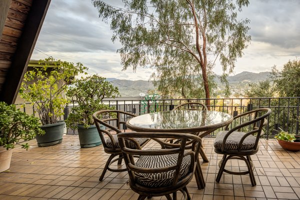 The semi-sheltered terrace allows for outdoor dining with views of the surrounding neighborhood and nearby mountains.