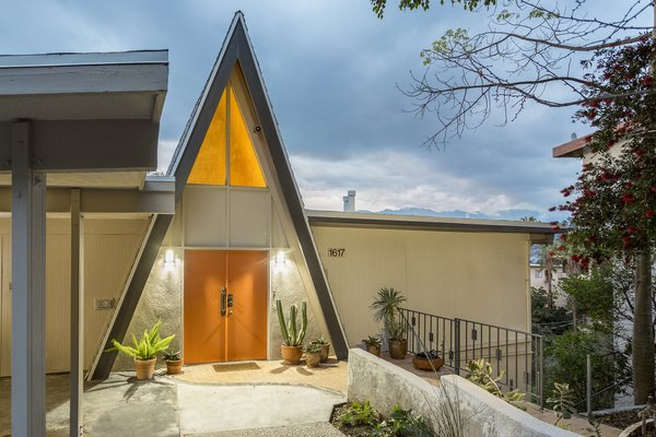 Set back on a quiet street, the orange double doors on the triangular facade echo the warm glow of light streaming through the window.