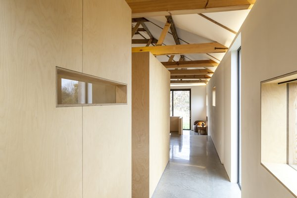 Simple plywood, cut out to allow views of the landscape, creates subdivisions within the home for private bedroom and bathroom spaces. Rather than formal rooms, they have the effect of large-scale furniture.