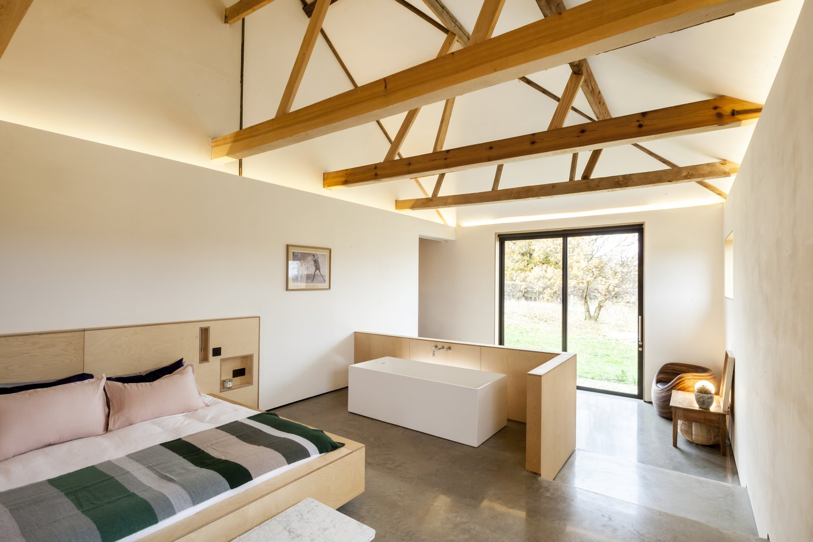 The master bedroom features an ensuite tub. Tagged: Bedroom, Bed, and Concrete Floor.  Photo 10 of 10 in This Converted Barn in the English Countryside Stays True to its Historic Roots