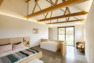 "The master bedroom features an ensuite tub. ""It's very utilitarian,"" says Witt of the barn conversion. ""A lot of people want eight bedrooms, but there's no need."" Agrees Smith, ""The space is the luxury."""