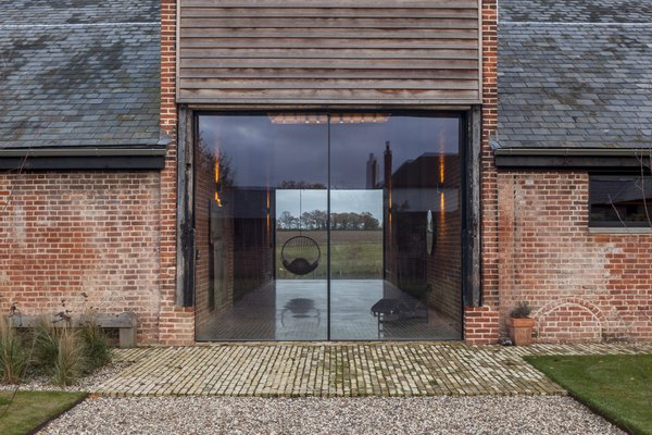 """Two oversized glazed doors welcome guests into Church Hill Barn. """"We wanted it to look like the barn doors were open,"""" says Witt. Reclaimed brick paves the doorway."""