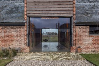 "Two oversized glazed doors welcome guests into Church Hill Barn. ""We wanted it to look like the barn doors were open,"" says Witt. Reclaimed brick paves the doorway."