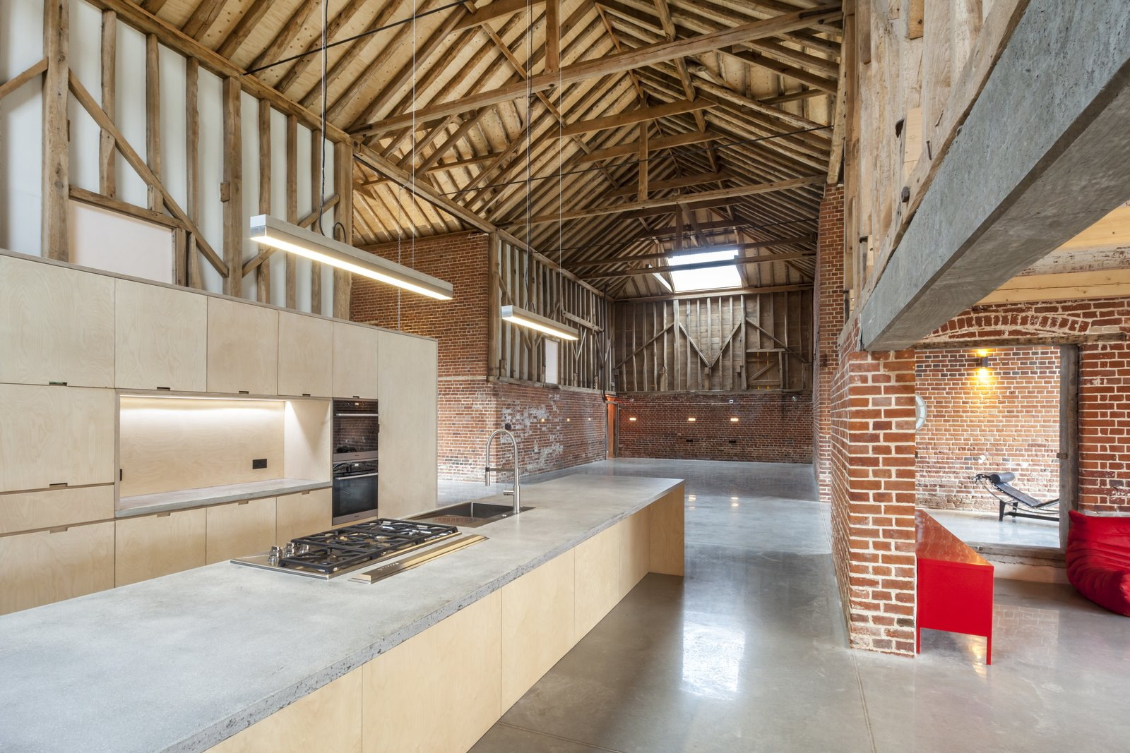 The kitchen is a minimalist, functional space with Miele and Wolf appliances, Lumi joinery, and concrete worktops and sinks designed by the homeowners. Tagged: Kitchen, Concrete Counter, Concrete Floor, and Wood Cabinet.  Photo 6 of 10 in This Converted Barn in the English Countryside Stays True to its Historic Roots