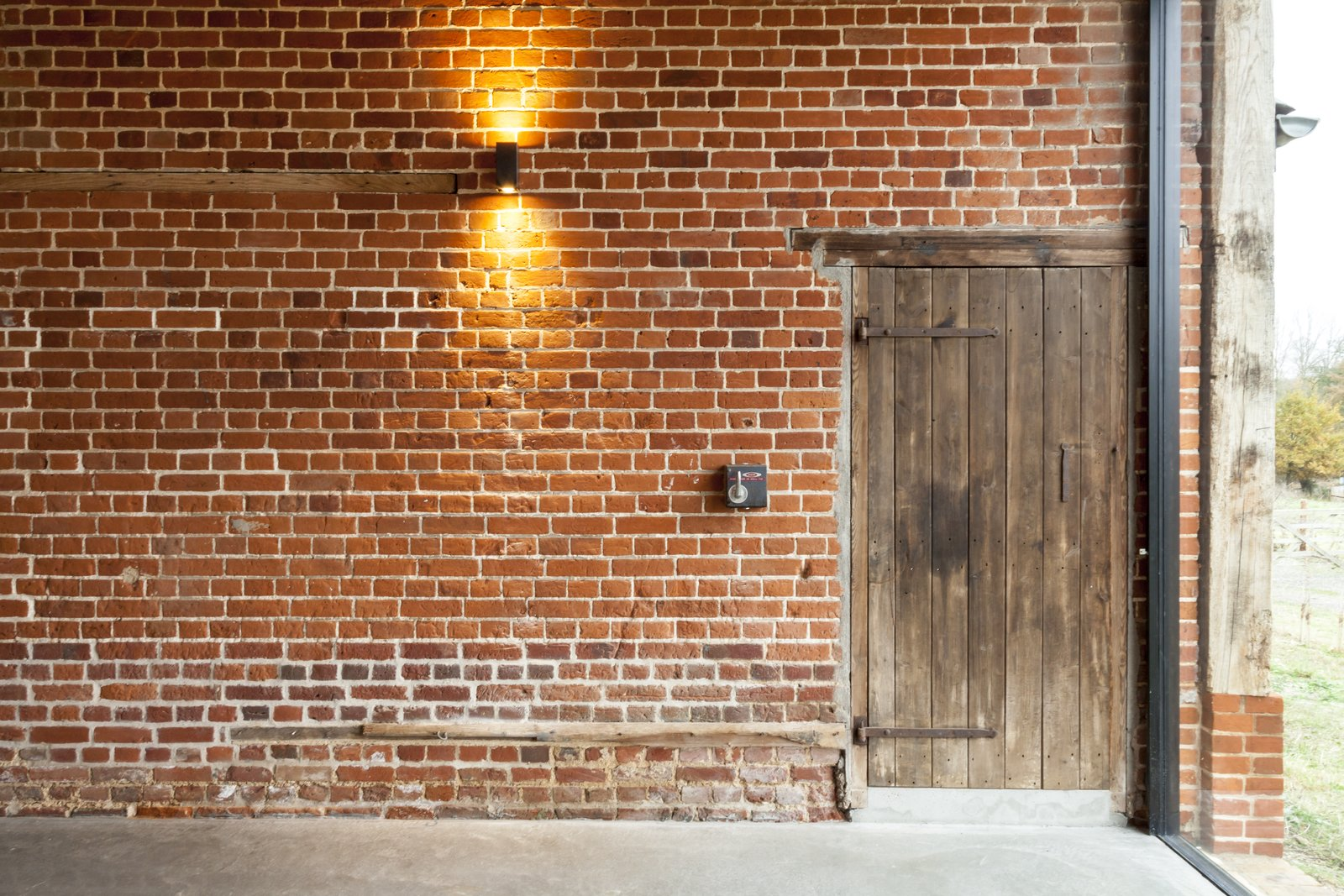 The lights are operated by original switch boxes. Beside it, a barn door leads to the three bedrooms. This Converted Barn in the English Countryside Stays True to its Historic Roots - Photo 8 of 10