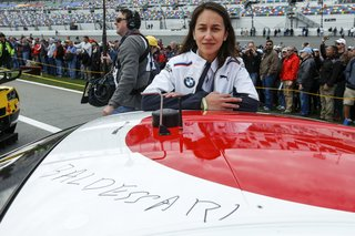 "John Baldessari Blazes a Trail at the Daytona International Speedway With BMW Art Car #19 - Photo 6 of 11 - McGough poses with the car, which bears Baldessari's signature. ""Having never been [to a race] before, I naively thought the sound of a car would be overwhelming, but it was exhilarating,"" she says of the Rolex 24. ""It just made my heart pump."""