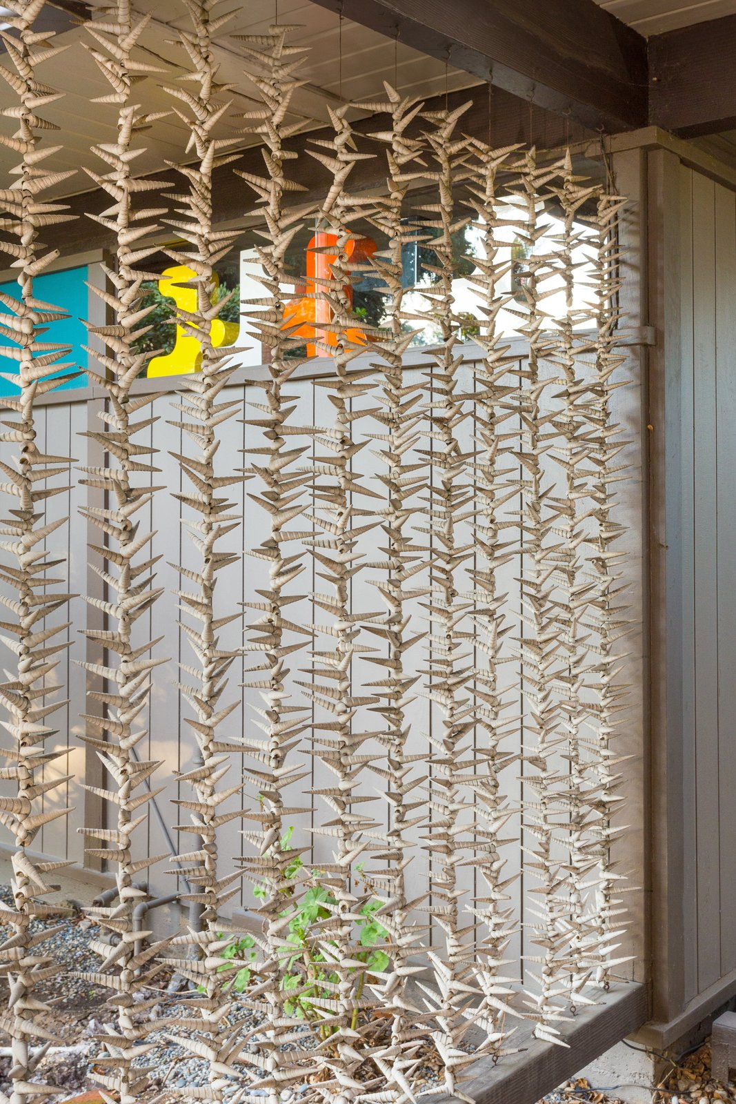 Strung seashells make up an organic screen for the carport, a natural touch added by the seller.  outdoor spaces by Adrian Wieland from Snag This Midcentury Stunner in Southern California For $799K