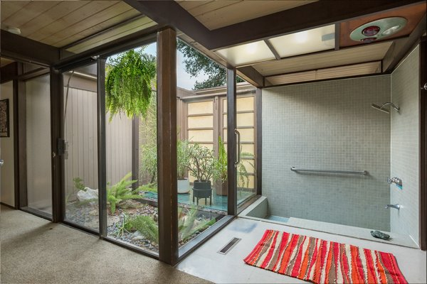 The sunken tile tub and shower in the ensuite master bathroom enjoys an outdoor connection in the form of a small atrium.