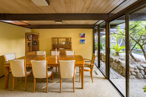 Homeowners can choose to eat in the dining room, pictured above, or bring their meal to a glass-encased lanai that looks out at the grassy backyard.