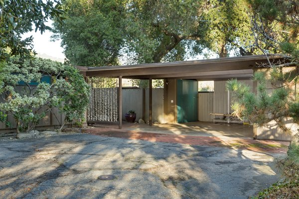 Set back from the street, the home provides privacy and seclusion. At the entrance, a carport leads to a brick-paved walkway that stretches to the front door.