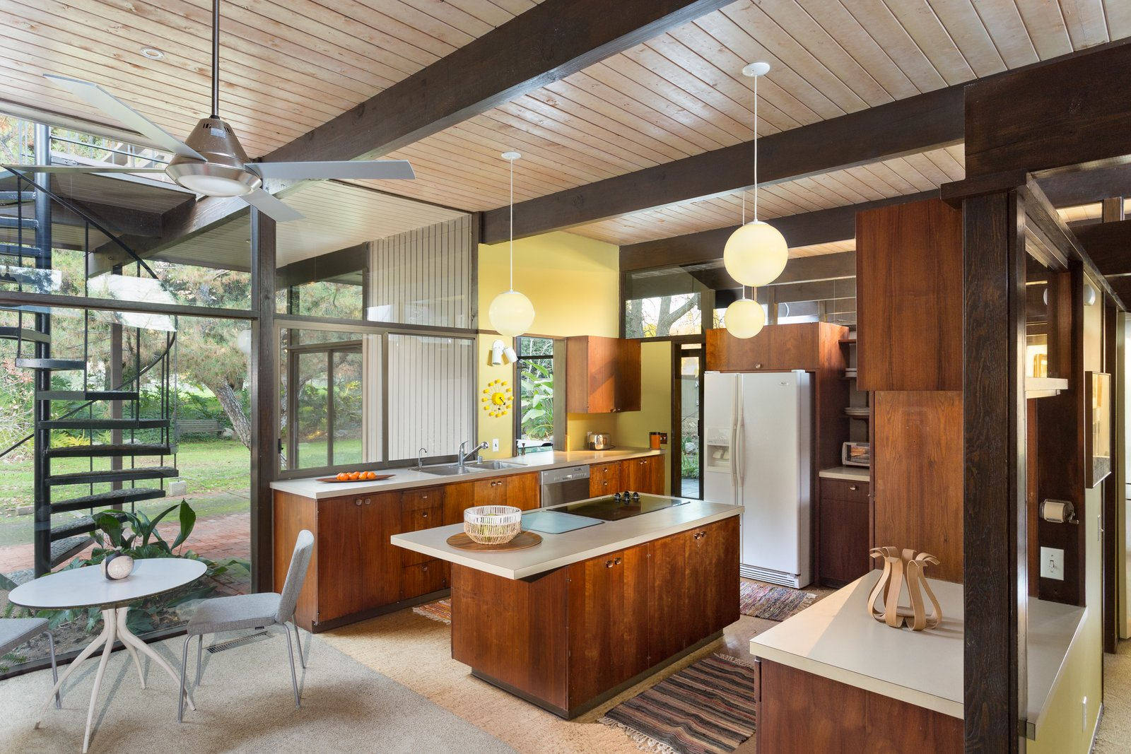 Carpeting, cork, and tile flooring run throughout the house, which is T-shaped in floor plan.