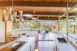 "From the kitchen, you step out onto a side patio, which has an opening cut into the roof to allow sunlight to fall on a planter. The previous owners, in an attempt to remodel the house in the Spanish style, had gutted the kitchen. Eric Lamers rebuilt the space with cabinetry based on elevation drawings found in Neutra's ""spec book,"" making changes according to practicality and building codes. Barbara Lamprecht helped the homeowners choose Porous Stone by Dunn Edwards for the paint. Believing that Neutra would have chosen modern fixtures, they installed a GE Monogram built-in refrigerator, wall oven, and induction cooktop. A KWC Suprimo faucet and Blanco sink complete the kitchen."