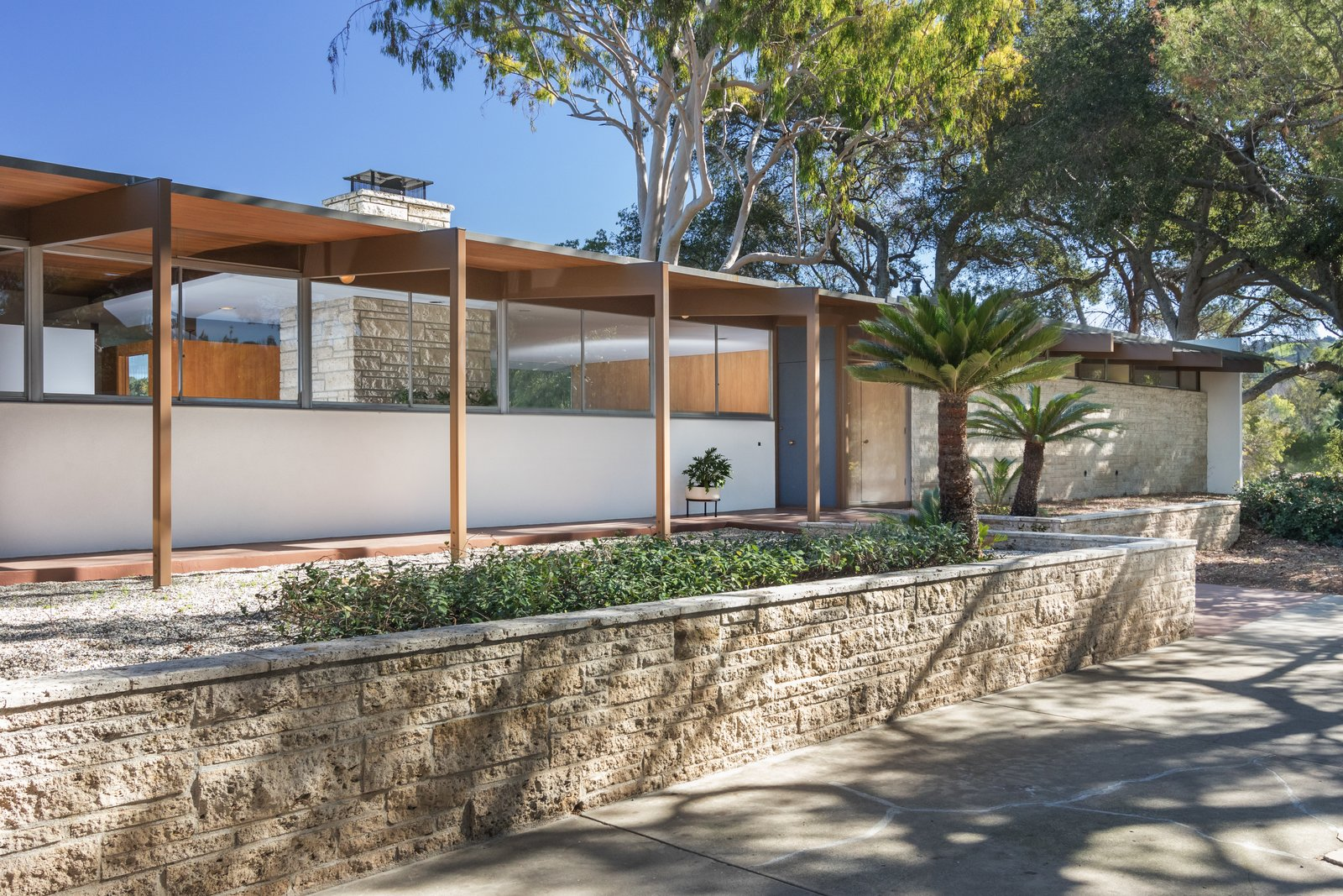 Originally sited on 14 acres of avocado and lime trees, the 2,580-square-foot residence was designed by Richard Neutra for James Roberts, a successful businessman in the manufacturing business, and his wife in 1955. A horse and several sheep roamed the property. Listing agent Nate Cole shares this anecdote: Tagged: Outdoor, Front Yard, and Trees.  Photo 2 of 9 in Nearly Slated For Destruction, a Restored Neutra in West Covina Asks $1.8M