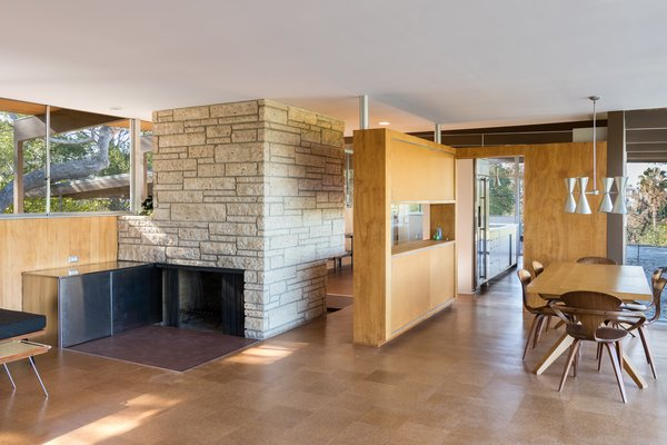 "Nearly Slated For Destruction, a Restored Neutra in West Covina Asks $1.8M - Photo 4 of 8 - A stand-alone Texas shellstone fireplace divides the living and kitchen areas. The stainless steel wood storage boxes had been removed, so the current owners had it fabricated to Neutra's specifications. They also scraped off the ""popcorn"" or ""cottage cheese"" ceilings and went so far as to hunt down Schlage Plymouth door knobs and locks in bronze. Under Lamers' direction, a team of carpenters sanded each ceiling board, custom-milling and replacing about 20 percent that were beyond repair, and removed dark stain from the birch wall paneling."