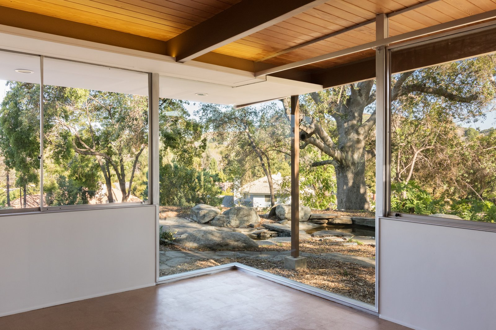Situated on the eastern end of the residence, the master bedroom boasts a mitered glass corner window that overlooks a koi pond and a Live Oak tree. Tagged: Outdoor, Side Yard, and Trees.  Photo 6 of 9 in Nearly Slated For Destruction, a Restored Neutra in West Covina Asks $1.8M