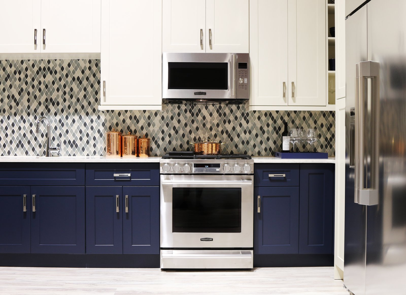 The Signature Kitchen Suite Smart Kitchen is outfitted with navy and ivory cabinets by Green Forest Cabinetry and a glass tile mosaic backsplash. For Fuller, who comes from a product design background, the