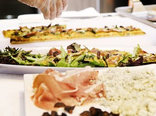 Signature Kitchen Suite's Modern Pavilion Shines at KBIS - Photo 7 of 7 - Flatbread topped with prosciutto, stilton cheese, figs, and arugula was part of the menu at Signature Kitchen Suite's impressive 4,000-square-foot exhibition booth.