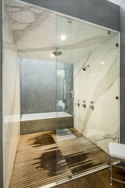 A deep soaking tub complements a shower lined with marble and wooden slats. A double vanity sits opposite.