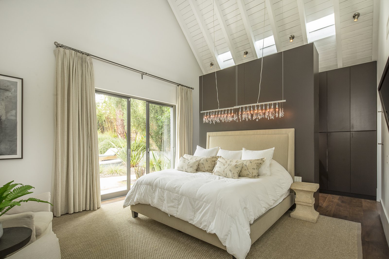 Like all the bedrooms and bathrooms, the master bedroom has electric venting skylights, as well as a sliding door that leads to the back patio.  Photo 7 of 10 in For the Entertainer, This $5.5M Home in Southern California Fits the Bill