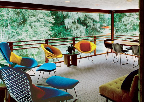 Bird Chairs, Diamond Chairs, and Dining Chairs by Harry Bertoia provide ample seating on this cantilevered porch, which is screened in by a delicate copper mesh and provides views of the expansive Dow Gardens—connected to the studio by an Asian-inspired footbridge.