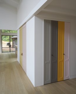 "Playful panels of color on closet doors and the stair risers break up the white walls. The homeowner explains, ""I took as inspiration Imi Knoebel, whose work I had seen at the Dia Beacon, and who works with large shapes of color placed in relationship to one another."""