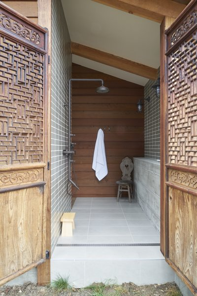 """The home offers places for solitude and quiet. """"Each bedroom was thought of as a separate building,"""" says the homeowner. """"Each bathroom had an outdoor component."""" Here, an outdoor shower is a private connection to the outdoors."""