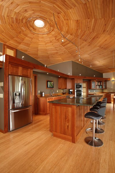 Empowered to act as his own general contractor with Deltec Homes' support, Sanders cut wood from his own property for the ceiling, trim, and cabinetry—drying, forming, and finishing the material on site.